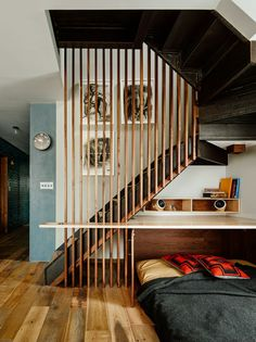 In Vinegar Hill, architect Sarah Zames transforms two unremarkable apartments into one modern space full of color and texture. She carved out a small custom office area under the stairs that leadup to the roof.The cabinet under the built-in desk opens to reveal a fold-outbed for guests.  Photo by Joe Fletcher .   This originally appeared in Two Apartments Were Combined into This Inviting Brooklyn Home.