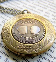 """Stamped with flowers and stripes, the token on this locket reads, """"Going steady,"""" how lovers referred to dating exclusively back in the day. The vintage-inspired image is set on an antiqued brass circular locket, left blank to fill with your own photos, notes or treasures."""