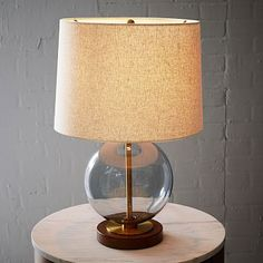 "Lawson Table Lamp $169 [Smoke or Clear?] 13""diam. x 20""h. •Glass; Acorn-finished wood base. •Antique Brass-finished metal accents. •Natural linen shade."