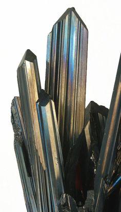 Teilweise buntfarbig angelaufene, langprismatische Stibnitkristalle mit typischer Längsstreifung aus der Ichinokawa-Mine, Japan Gesamtgröße der Stufe: 37 × 9 × 7,5 cm