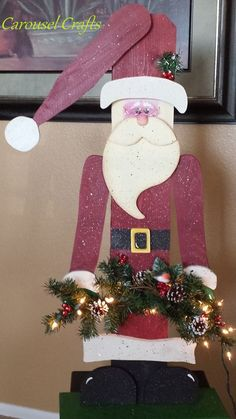 Wood Craft Santa. With greenery and lights.  Santa has glasses, spectacles. Rustic Santa. Old time Santa