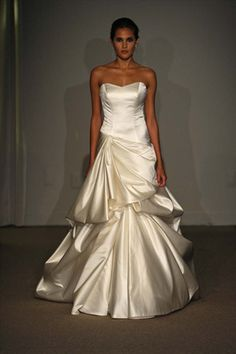 DESIGNER: Anna Maier STYLE: Anouk NECKLINE: Strapless Sweetheart SILHOUETTE: Aline FABRIC: Duchess Satin COLOR: Ivory FEATURES: Duchess satin, asymmetrical bodice Aline gown, draped skirt, extended train TRAIN: Chapel CONDITION: Sample from boutique, no rips, tears, or stains SIZE: 10 PRICE: $2,500.00