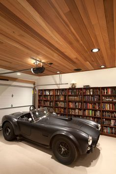 Cobra in a library. Paneled ceiling and bookshelves filled with automobilia.