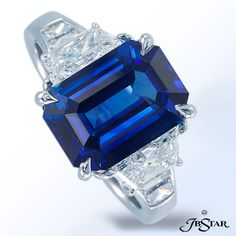 JB Star Platinum sapphire and diamond ring with a stunning 4.87 ct emerald-cut blue sapphire embraced by trapezoids and additional trapezoids in the shank. Center: Emerald-cut Blue Sapphire 4.87ct Diamonds: Trapezoid 1.71 ctw