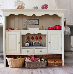 DIY kitchenette: Dresser hutch, lasagna pan 'sink', salvaged faucet w/ knobs. Stovetop burners? Made with old CDs! Miniature old kitchen tools. Toy cupboard items from old packages (like cardboard boxes, tins, etc.). SOOOOOO cute!