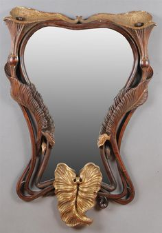 PAIR OF ART NOUVEAU STYLE CARVED WALNUT AND PARCEL-GILT MIRRORS   Each shaped plate within pierced frame, carved with calla lillies and entwined foliage. 4 ft. 6 in. x 37 in.   Estimate $ 2,000-3,000