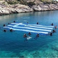People swimming in the sea in Lindos Rhodes Greece with the Greek Flag On Greek Independence Day Most Beautiful Beaches, Beautiful Places, Greek Independence, Myconos, Greece Pictures, Greek Flag, Corfu Island, Family Vacation Spots, Greece Islands