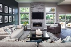 Big open windows lets in tons of natural light in a gray, modern living room. A black accent wall with black-and-white photographs make a bold statement. Neutral furniture keeps the space feeling light and fresh. Coastal Living Rooms, Home Living Room, Living Room Designs, Living Room Furniture, Living Room Decor, Apartment Living, Dining Rooms, Family Room Design, Gray Family Rooms