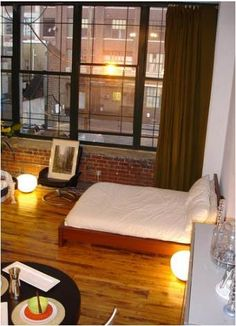 """Note to real estate agents: this is what a """"New York style apartment"""" actually looks like. Wooden floors, dark mixed with natural lightening trough large windows, cozy and warm lights. New York Studio Apartment, Nyc Studio Apartments, New York Apartments, Studio Apartment Decorating, Dream Apartment, Apartment Interior, Apartment Design, Small Apartments, Apartment Living"""