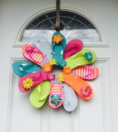 """Flip Flop Color-block Stripes Sun Fun, Decorate your door or room with the summer footwear we love to wear. This wreath is fastened with greening pins making it sturdy and heat resistant. The wreath measures approximately 22"""" across, includes 12 youth flip flops and comes with a variety of flower embellishment's. Please avoid displaying this wreath in between a storm and house door. Too much direct sunlight causes extreme heat built up."""