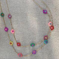 Collier long de petites fleurs multicolores tissées sur une