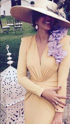 Invitada perfecta con vestido amarillo y detalles flores de seda malva acompañado por maxi Pamela