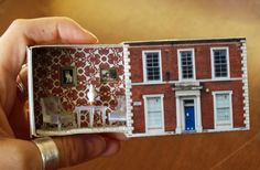 A large matchbox is given a makeover to become a cute little room that can fit in your hand. Photographs cover the box and tiny furniture is