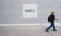 "Man in hat walks in front of wall with zig zag pattern and a ""Harry's"" sign"
