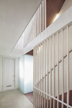 Latticed wooden screens form balustrades for a red pigmented concrete staircase inside this renovated mews house in west London