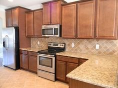 Image result for cinnamon cabinets tan granite tumbled marble backsplash