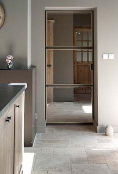Simple industrial door.  The split glass panels offset white, rustic interiors.