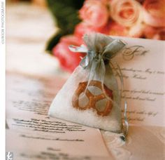 """Guests also loved the uniquely personal, homemade favors -- silver sachets filled with salt and a pretzel. The attached card read: """"In Germany, a year of good luck is ensured when the couple eats salt and bread. Salt provides the couple with a life of blessings and good luck."""" Printed on the reverse was a recipe for laugenbrezel -- Marc's favorite German pretzel."""
