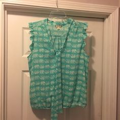Green top with elephant designs! Green top with white elephant design. Cute tie in the front with precious ruffles on the sleeves. Tops Blouses