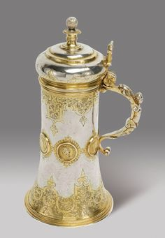 HANS HENSSEL ROMANIAN PARCEL-GILT SILVER TANKARD  inverted trumpet shape, engraved with arabesques in strapwork and inset with casts of six antique coins, armorial engraved, initialled DBK on a stylized animal skin for the guild of Furriers and dated 1605, maker's mark only, later French control marks  24.5cm, 9 5/8 in high  634gr, 20oz 6dwt  Sibiu (Hermannstadt), circa 1605