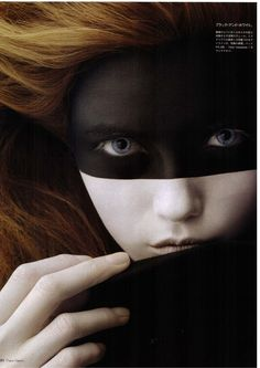 Dramatic black makeup like a mask over half of face, white other half of face. Blue eyes, blondy-brown hair.