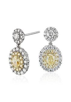 Stunning oval-cut yellow diamonds surrounded by concentric halos of round yellow and white diamonds create these remarkable earrings.