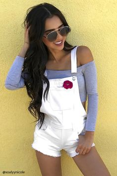 A pair of denim overall shorts featuring adjustable straps, a bib patch pocket, five-pocket construction, a belt looped waist, a buttoned side, and a distressed frayed hem.