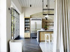 Modern kitchen with exposed brick, mis-match floors, and a industrial fridge