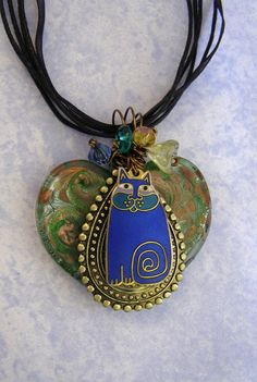 """One of a Kind Vintage Laurel Burch Blue Cat Necklace- Lampwork Glass Pendant-Wire Wrapped Jewelry-Recycled Jewelry-Gift for Cat Lovers  An artist creation- a recycled gold plated blue Laurel Burch cat -recycled into a one of a kind piece of art jewelry. I handcrafted this piece using a vintage Laurel Burch cat, wire, a lovely gold and green swirled heart shaped lampwork glass. I also added glass beads at the top.  The pendant measures about 1 1/2"""" long and 1 3/4"""" wide."""
