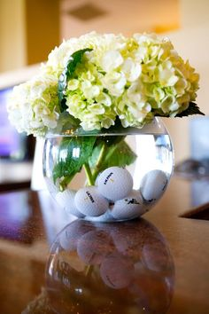 Golf birthday party centerpiece made with a glass vase, green hydrangea, and golf balls.