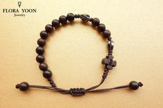 ♥ Knotted Wood Rosary bracelet for you ♥  This bracelet is a unique style rosary bracelet!  It is using good-quality 6mm Hematite beads, 8 mm or 10mm dark brown round date tree wood beads (which belongs as a tree to a family of rose tree), 12 mm dark brown date tree wooden cross.  Rosary bracelet Size: Approximately 7 to 11 inches(18 to 28 cm). (Adjustable)  This bracelet is easy to wear. Comes with Good Velvet pouch ready for giving! Beautiful gift idea for Confirmation, First Communion or…
