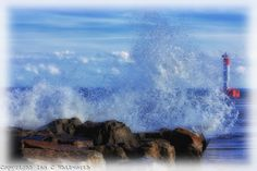 An artistic view of the waves splashing against the rocks at the base of the Oakville lighthouse pier.