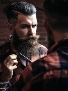 65079093 - young man hipster with handsome bearded face brunette cutting long fashion beard with scissors looking in mirror