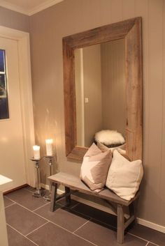 Large framed mirror hung above rustic wood bench