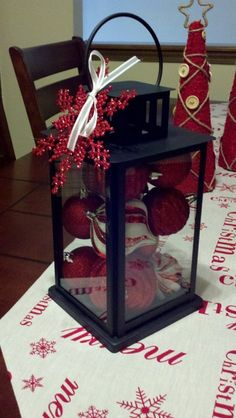Lantern from Lowes for $1.50 filled with Christmas ornaments already on hand!  OR~ fill the lanterns with autumn decor (leaves, twigs pinecones) OR~ fill the lanterns with Easter eggs, or spring decor. Buying a few of these lanterns can be part of almost every holiday's decor! Lots of uses!