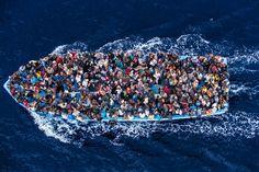<strong>7 juni</strong> Twaalf dagen bracht fotograaf Massimo Sestini door aan boord van een Italiaans fregat, op humanitaire missie op de Middellandse Zee. Vanuit de helikopter ontdekten ze deze boot met naar schatting 500 vluchtelingen, op weg naar het beloofde land. Volgens de fotograaf begonnen ze bij het zien van de helikopter te roepen en te zwaaien, eerst wanhopig, en toen al heel snel opgelucht om de nabije redding. Als je goed kijkt zie je heel veel. Een Argentijns voetbalshirt, ...