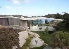 This island holiday home by Lund Hagem is sheltered beneath a wide concrete canopy, which bridges surrounding rock formations to frame views to the coast