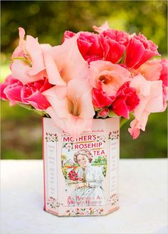 pretty pink and coral flowers in a vintage tin can