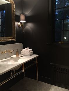 carrera marble hex floor black walls and trim unlacquered brass fittings