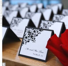 black, white, and red decor was accented with a signature H monogram, which appeared throughout the reception. The escort cards were made from white pearl paper, and the table where they were presented was peppered with bold crimson-hued roses.