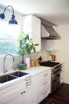 Amazing kitchen with creamy white kitchen cabinets with white quartz countertops, carrara marble tiles backsplash and blue sconce.