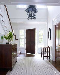 A striped carpet ties together the entrance hall's white walls and dark-wood elements.