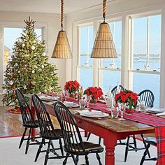 This Stonington, Connecticut, dining room is dressed to impress for the holidays with a simple poinsettia centerpiece, plaid table runner, and gorgeous Christmas tree.