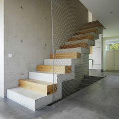 Particolare scala in cemento in cui ogni secondo gradino è realizzato da blocchi di quercia, alternando i toni caldi del legno con quelli freddi del cemento. La ringhiera è creata da una rete d'acciaio che serve da protezione