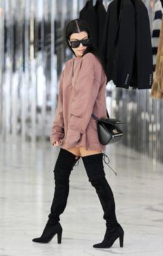 On Kourtney Kardashian: Givenchy Mini Pandora Box ($2290); Yeezy sweatshirt; Stuart Weitzman Highstreet Boot ($798).