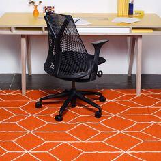 Retro, geometric-patterned, orange rug.