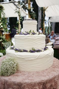 The bride's baby's breath bouquet accompanies a three tiered wedding cake.