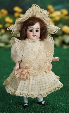 "7"" Pretty German All-Bisque Doll, Model 886, by Simon and Halbig~~~peg-jointed bisque arms and legs, painted above-the-knee blue stockings, black one-strap shoes with sculpted bows. Marks: 886 2. Comments: Simon and Halbig, circa 1890. Value Points: beautiful face with entrancing large eyes, all-original parts, fine original costume."