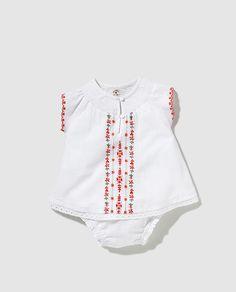 Vestido en color blanco, de manga corta y cuello caja. Cierre de botones en el delantero y detalle de nido de abeja. Adorno de bordados a contraste. Incluye cubrepañales en color blanco.