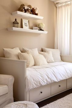 Gender neutral nursery features walls painted tan, Benjamin Moore Everlasting, lined with stacked shelves over a white beadboard daybed, Ikea Hemnes Daybed, dressed in  tan monochromatic pillows.